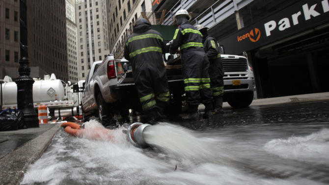 Water is pumped from a subterranean parking garage in New York's Financial District, Friday, Nov. 2, 2012. Sandy, the storm that made landfall Monday, caused multiple fatalities, halted mass transit and cut power to more than 6 million homes and businesses.(AP Photo/Richard Drew)