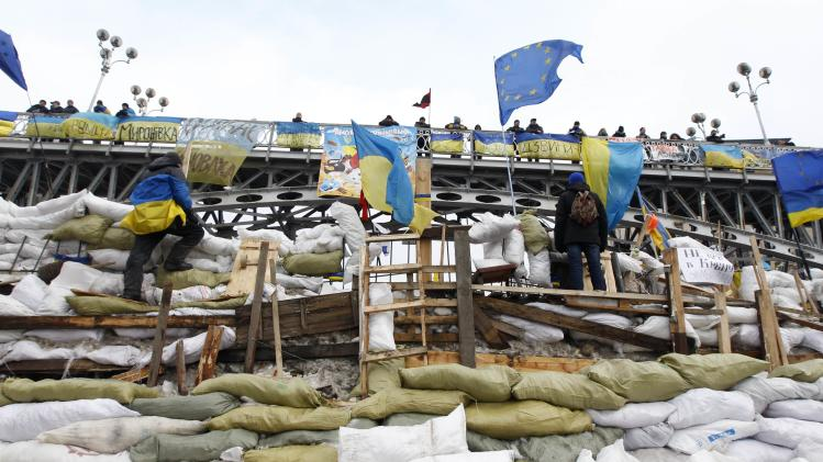 Pro-European integration protestors gather at a barricade in central Kiev