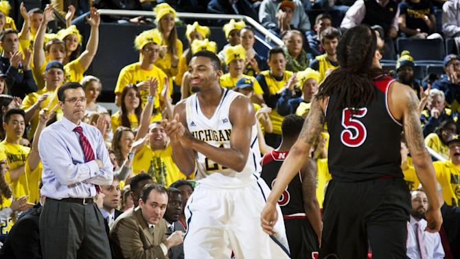 Nebraska head coach Tim Miles, left, watches Michigan guard Zak Irvin (21) and Nebraska guard Terran Petteway (5) react after a play in the second half of an NCAA college basketball game at Crisler Center in Ann Arbor, Mich., Tuesday, Jan. 27, 2015. Michigan won 58-44. (AP Photo/Tony Ding)