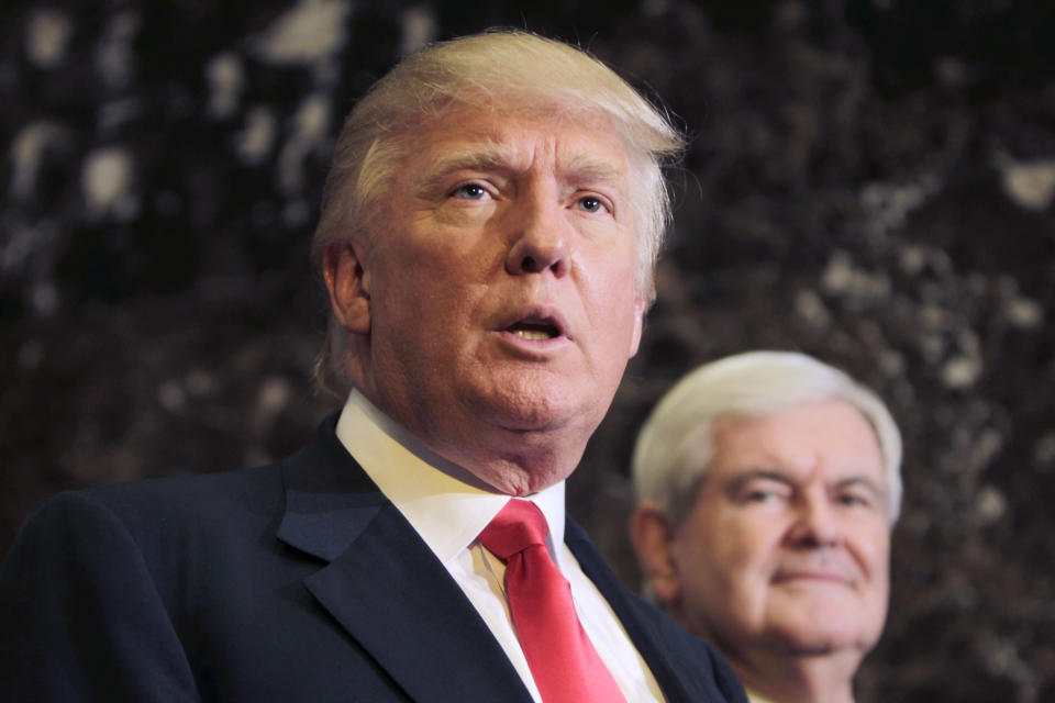 Republican presidential candidate, former House Speaker Newt Gingrich listens at right as Donald Trump talks to media after a meeting in New York, Monday, Dec. 5, 2011.  (AP Photo/Seth Wenig)