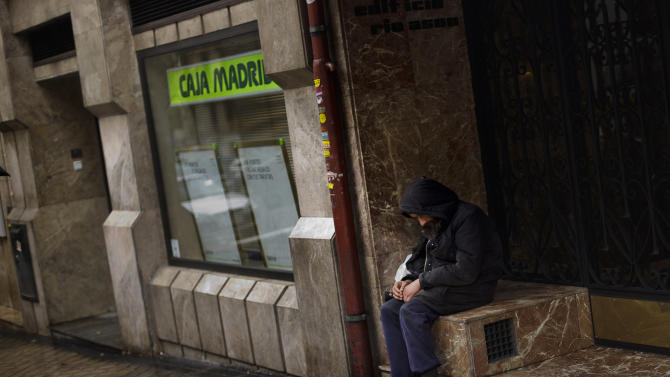 A homeless man sits near a Caja Madrid bank office in Madrid, Tuesday Oct. 30, 2012. Spain's National Statistics Institute says Tuesday that the country's economy contracted 0.3 percent in the third quarter from the previous three month period. Spain is in a double-dip recession and has a 25 percent unemployment rate. Prime Minister Mariano Rajoy said Monday the country has no immediate need to ask for outside aid to help deal with its debts. (AP Photo/Daniel Ochoa de Olza)