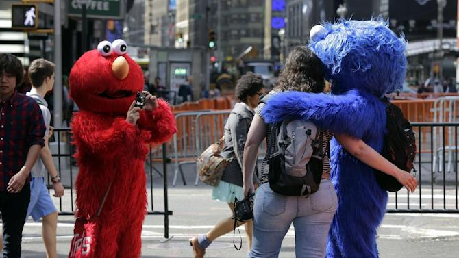 An Elmo character, left, uses a woman's camera to photographer her with a Cookie Monster character, in New York's Times Square, Tuesday, April 9, 2013.  A string of arrests in the last few months has brought unwelcome attention to the growing number of people, mostly poor immigrants, who make a living by donning character outfits, roaming Times Square and charging tourists a few dollars to pose with them in photos. (AP Photo/Richard Drew)