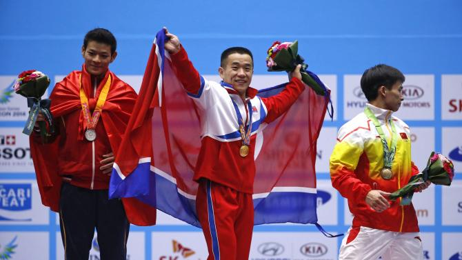 North Korea's Om reacts on the podium after winning the men's 56kg weightlifting competition during the 17th Asian Games in Incheon