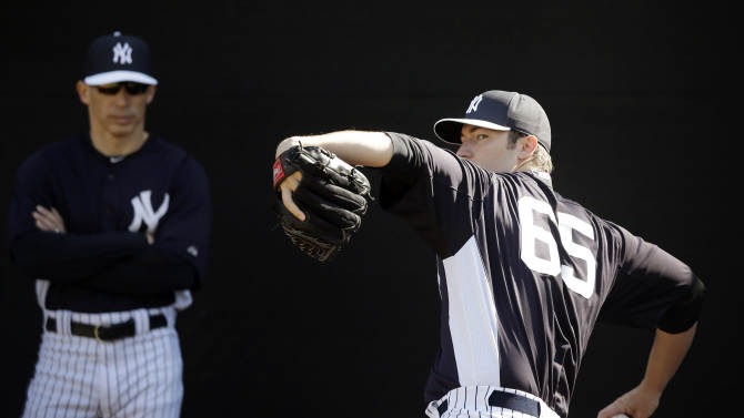 """FILE - In this Feb. 16, 2013 file photo,New York Yankees' Phil Hughes, right, pitches as manager Joe Girardi looks on during a workout at baseball spring training in Tampa, Fla. Hughes could be sidelined for two weeks because of a bulging disk that will be treated with anti-inflammatory medication. """"I'm convinced I'll be symptom free in the next four or five days,"""" Hughes said Wednesday, Feb. 20, 2013. (AP Photo/Matt Slocum, File)"""