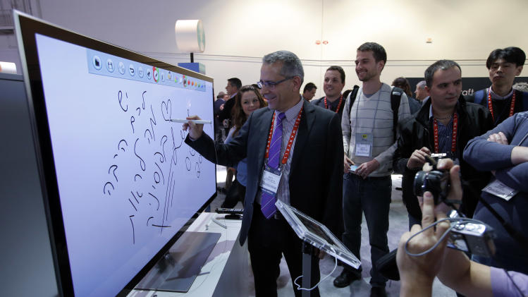 Moti Elmaliach, center, of Israel, writes on a display using Panasonic's electronic touch pen at the Panasonic booth at the International Consumer Electronics Show in Las Vegas, Tuesday, Jan. 8, 2013. (AP Photo/Jae C. Hong)