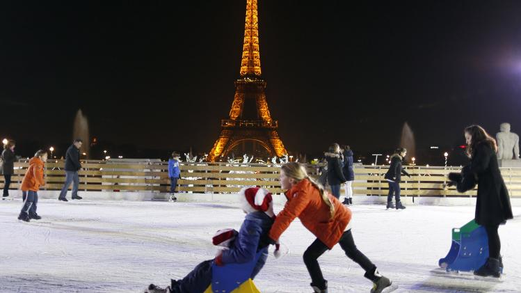 People skate on an ice skating rink across from the Eiffel Tower as part of the holiday season, in Paris