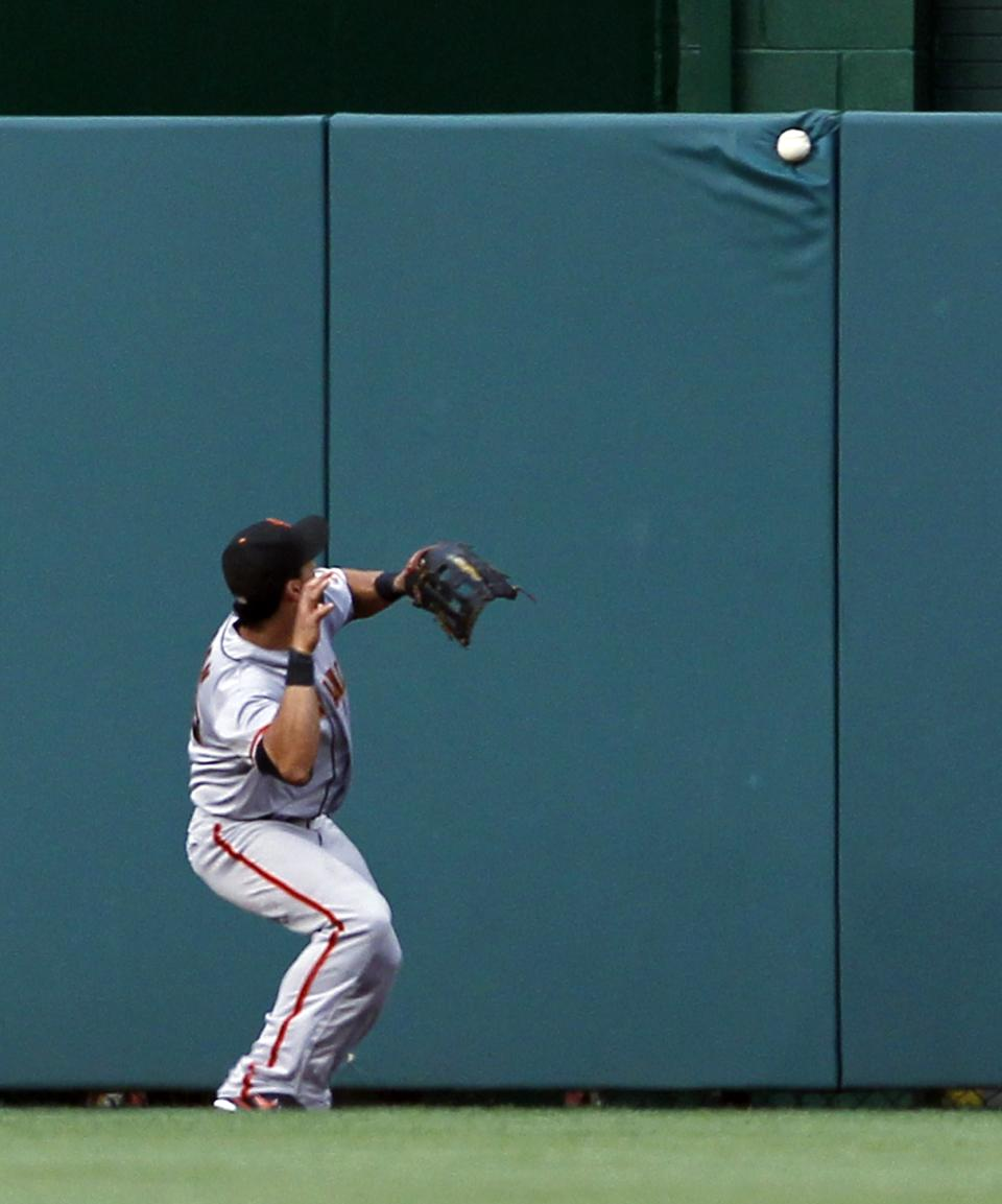 San Francisco Giants center fielder Angel Pagan waits to play the ball off the wall from Washington Nationals' Danny Espinosa, who hit a one-RBI double, during the second inning of a baseball game, Tuesday, July 3, 2012, in Washington. (AP Photo/Alex Brandon)