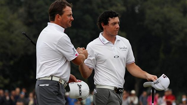 Rory McIlroy (R) of Ireland celebrates with teammate Graeme McDowell after playing on the 18th green during the third day of the Mission Hills World Cup golf tournament in Haikou, China's Hainan province