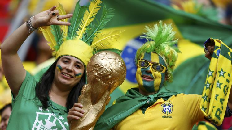 Brazil fans pose before the 2014 World Cup Group A soccer match between Cameroon and Brazil at the Brasilia national stadium