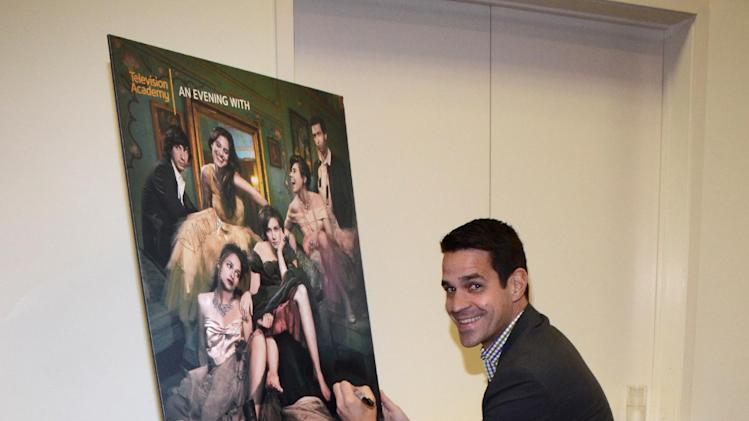 "EXCLUSIVE - Dave Karger, chief correspondent for Fandago, signs a poster at ""An Evening with GIRLS"" on Thursday, March 13, 2014, at the Television Academy in the NoHo Arts District in Los Angeles. (Photo by Tonya Wise/Invision for the Television Academy/AP Images)."