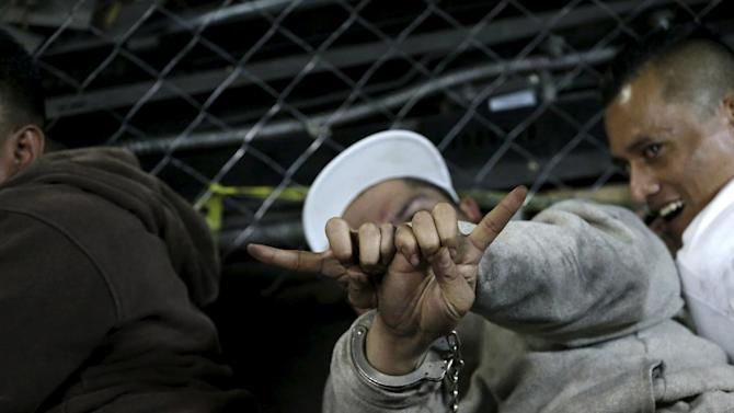 A member of the Mara Salvatrucha criminal gang flashes gang signs as he lies on the floor, after a shootout in the basement of the Supreme Court of Justice in Guatemala City