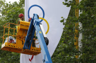 Workmen take down an Olympic flag in the Mall near Buckingham Palace in London, Monday Aug. 13, 2012, following the closing ceremony of the 2012 Summer Olympics. The London summer games ended late Sunday, with the next summer games scheduled to be in Rio de Janeiro, Brazil, in 2016. (AP Photo/Alastair Grant)