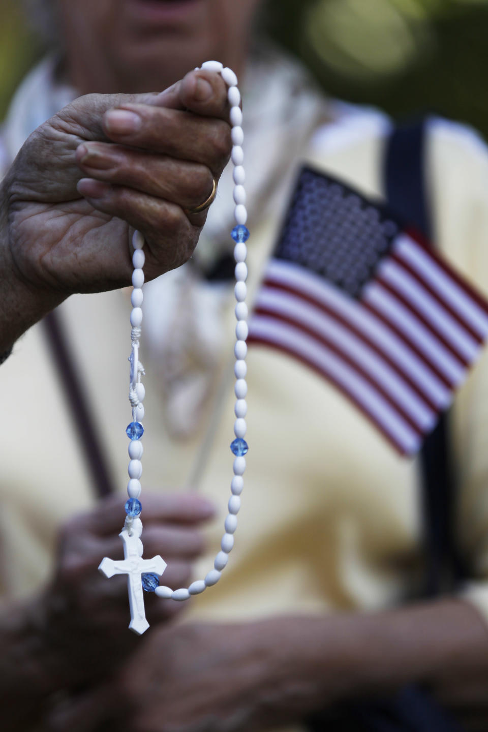 Demonstrators pray with rosary beads during a protest against the Obama administration mandate that employers provide workers birth control coverage, at Independence Mall, Friday, June 8, 2012, in Philadelphia. The event was organized by Stand Up For Religious Freedom. (AP Photo/Matt Rourke)