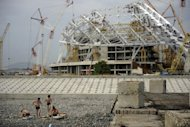 "Workers take a break near the 'Fisht' Olympic stadium, which is under construction for the Sochi 2014 Winter Olympics. Russia on Wednesday set itself the ""unbelievably"" tough target of finishing top of the podium at its home Winter Olympic Games after placing a humiliating 11th two years ago"