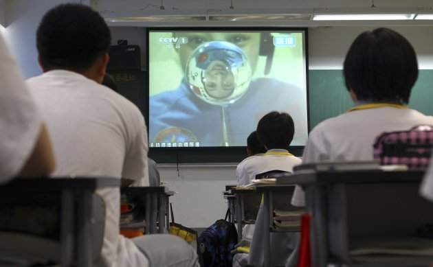 Students watch a live broadcast of a lecture given by Shenzhou-10 spacecraft astronauts on the Tiangong-1 space module, at a school in Beijing