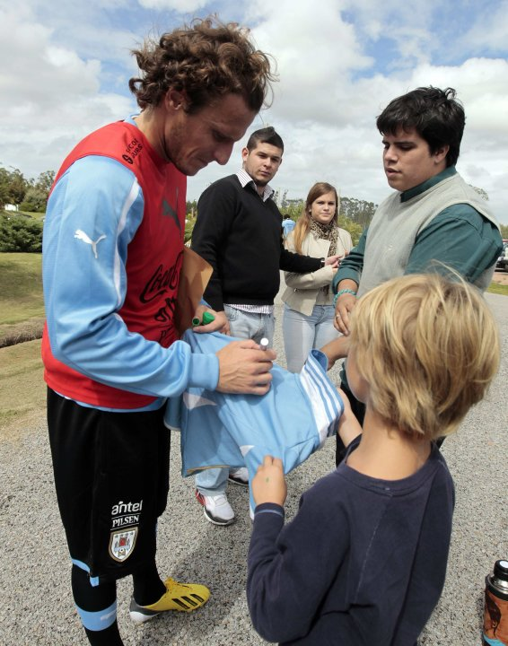 Uruguay's national soccer team player Diego Forlan signs autographs for fans after a training session in Uruguay