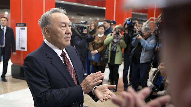 Kazakhstan's President and presidential candidate Nursultan Nazarbayev applauds during the opening of the Moscow station of the Almaty metro system