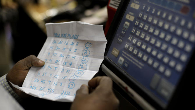 Convenience store clerk Woody Amlak inserts customer Javon Lee's Powerball numbers into a machine in Baltimore, Wednesday, Nov. 28, 2012. Lee, a manager of a local McDonald's restaurant who was playing Powerball for the first time, picked the numbers using a combination of family members' birthdays and addresses. (AP Photo/Patrick Semansky)