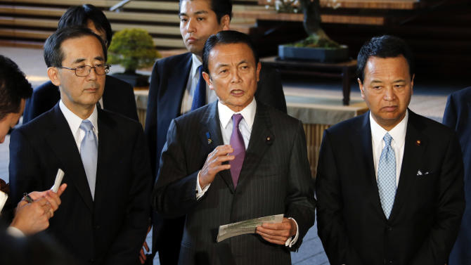 """Japan's Finance Minister Taro Aso, center, along with Economics Minister Akira Amari, right, and Bank of Japan Gov. Masaaki Shirakawa, left, speaks to the reporters after meeting with Prime Minister Shinzo Abe, not in photo, at the prime minister's official residence in Tokyo, Tuesday, Jan. 22, 2013. Japan's Prime Minister Abe declared a """"monetary regime change"""" Tuesday as the central bank bowed to government pressure, setting a 2 percent inflation target aimed at helping the country emerge from its prolonged bout of deflation. (AP Photo/Koji Sasahara)"""