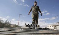 A soldier in the Syrian army walks on the top of a Russian-made armoured personnel carrier stationed on a street leading into of Maalula on September 18, 2013