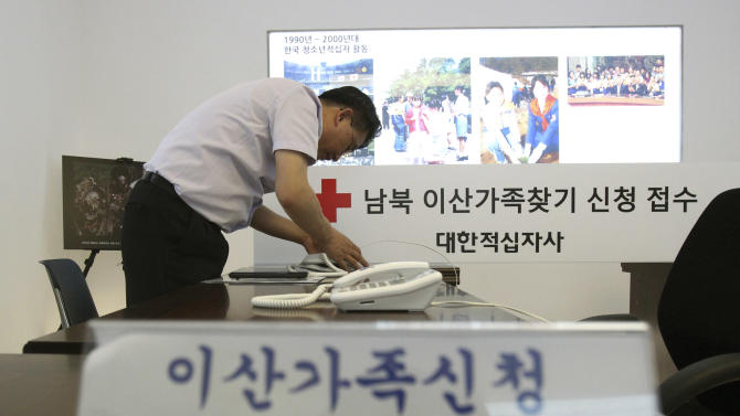 "A member of the Red Cross connects the inter-Korean communication line at the Korean Red Cross headquarters in Seoul, South Korea, Tuesday, June 11, 2013. The line was restored last week following North Korea's offer to hold talks with South Korea. The two Koreas will hold their highest-level talks in years Wednesday in an effort to restore scrapped joint economic projects and ease animosity marked by recent threats of nuclear war.  The Korean writing reads "" Applications reception of separated families. "" (AP Photo/Ahn Young-joon)"