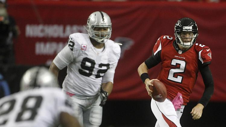 Atlanta Falcons quarterback Matt Ryan (2) runs for the first down against Oakland Raiders defensive tackle Richard Seymour (92) and Oakland Raiders defensive back Phillip Adams (28) during the second half of an NFL football game, Sunday, Oct. 14, 2012, in Atlanta. (AP Photo/John Bazemore)