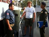 Cambodian military police escort Sergei Polonsky (centre) from a boat at Sihanoukville on Sunday. The real estate tycoon is among three Russian men arrested and charged in Cambodia over accusations they threatened and locked up the crew of a boat at knifepoint, an official said Friday