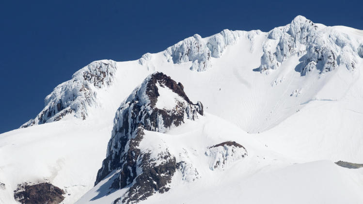 This photo taken Thursday, June 14, 2012 shows the area of Mount Hood where experienced climber Mark Cartier fell to his death earlier in the day. Cartier fell to the left, off of Hogsback, the u-shaped ridge on the right of the frame, and behind the large rock, Crater Rock, in center of photo. (AP Photo/The Oregonian, Brent Wojahn)
