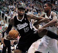 Sacramento Kings center DeMarcus Cousins (15) keeps Utah Jazz forward Derrick Favors, right, at bay while trying to control possession of a rebound during the first half of their NBA basketball game in Salt Lake City, Friday, March 30, 2012. (AP Photo/Steve C. Wilson)