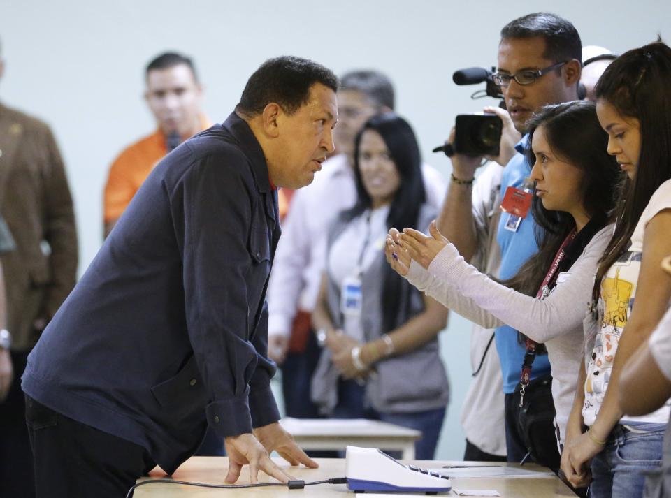 Venezuela's President Hugo Chavez, left, speaks with an electoral worker at a polling station before casting his ballot for the presidential election in Caracas, Venezuela, Sunday, Oct. 7, 2012. Chavez is running for re-election against opposition candidate Henrique Capriles. (AP Photo/Fernando Llano)