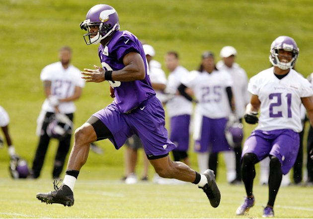 In this photo taken June 18, 2013, Minnesota Vikings running back Adrian Peterson carries the ball during NFL football minicamp at Winter Park in Eden Prairie, Minn. In training camp, an allergic reac