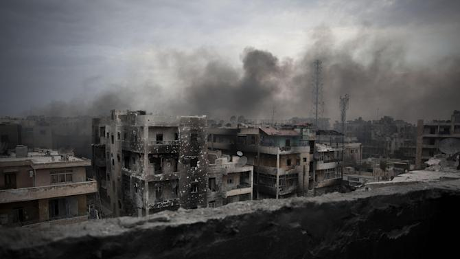FILE - In this Tuesday, Oct. 2, 2012 file photo, smoke rises over Saif Al Dawla district, in Aleppo, Syria. Nearly 19 months of violence in Syria have left their mark everywhere: Entire blocks of apartment buildings have been shattered, their top floors reduced to pancaked concrete. Centuries-old markets have been gutted _ billions of dollars along with an irreplaceable chunk of history wiped out in just few hours of battle. Oil pipelines, factories, schools, hospitals and churches and mosques have been systematically destroyed. (AP Photo/ Manu Brabo, File)