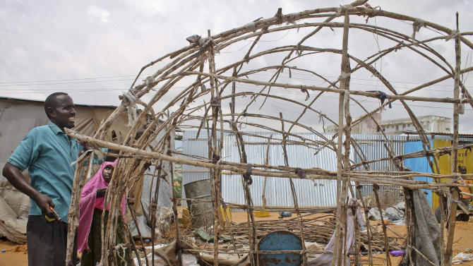 In this photo taken Friday, Nov. 30, 2012, a Somali internally-displaced person (IDP) removes his makeshift home in Sigale camp, Mogadishu, in Somalia. A year of relative peace in Somalia's capital has led to a property boom yielding higher rents and sale prices but the newfound prosperity is also incentivizing land owners to evict refugees - forcing thousands of families into the open and exposing women to sexual assault. (AP Photo/Farah Abdi Warsameh)
