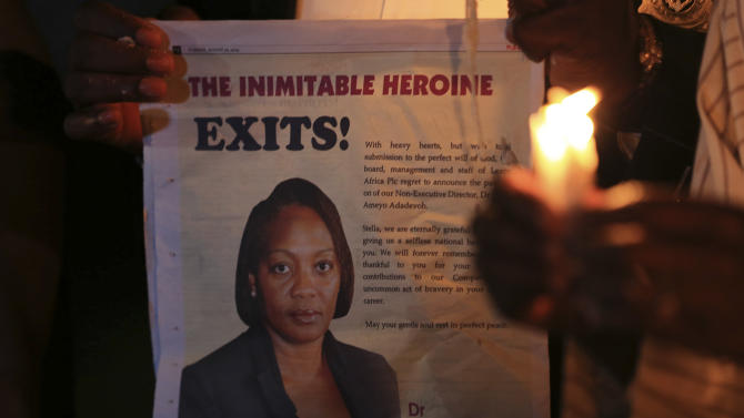 "A campaigner of ""#Bring Back Our Girls"" shows an image of Ameyo Stella Adadevoh during a candlelight vigil for Adadevoh and other Ebola victims in Abuja"