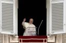 Pope Francis waves from the window of his study overlooking St. Peter's Square at the Vatican before leading his Sunday Angelus prayer on July 13, 2014
