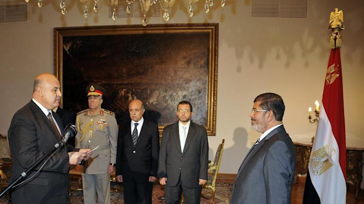 RETRANSMISSION FOR ALTERNATIVE CROP - Egyptian President Mohammed Morsi swears in newly-appointed vice president, a former senior judge, Mahmoud Mekki, in Cairo, Egypt, Sunday, Aug. 12, 2012. Egypt's Islamist president also ordered his defense minister and chief of staff to retire on Sunday and canceled the military-declared constitutional amendments that gave top generals wide powers. (AP Photo/Egyptian Presidency)