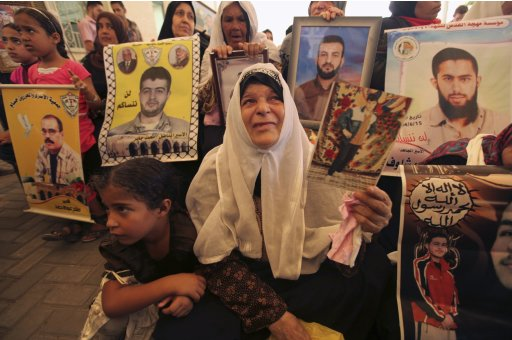 Palestinian women hold pictures of their jailed sons during a demonstration calling for their release at the International Red Cross headquarters in Gaza City