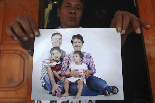 CLICK IMAGE for slideshow: Widi Yuwono, the brother of Yuli Hastini, right, shows her sister's family portrait with her Dutch husband John Paulissen and their two children Arjuna and Sri who were on board of the crashed Malaysia Airlines flight 17, at his residence in Solo, Central Java, Indonesia, Friday, July 18, 2014. The Malaysian jetliner that went down in war-torn Ukraine did not make any distress call, Malaysian Prime Minister Najib Razak said Friday, adding that its flight route had been declared safe by the global civil aviation body. (AP Photo)
