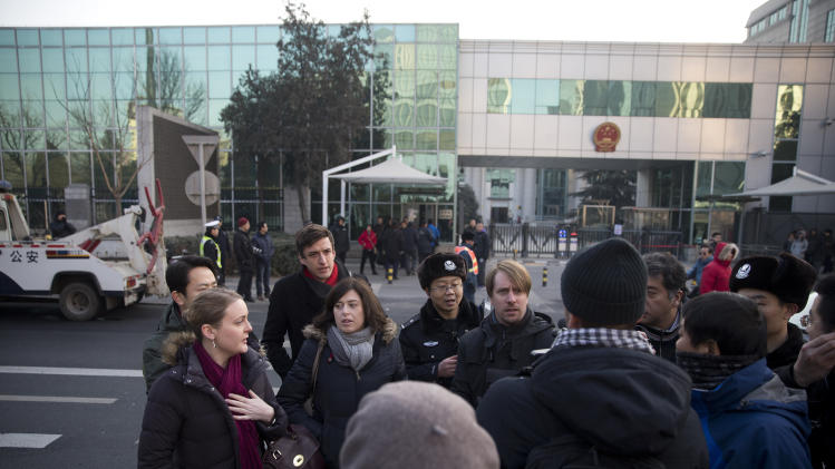 Chinese policemen try to block foreign diplomats talking to journalists as they prepare to attend a trial of Xu Zhiyong outside the Beijing's No. 1 Intermediate People's Court, China Wednesday, Jan. 22, 2014. The trial of the prominent activist who has led a grassroots campaign demanding a fairer society and official accountability to better fight corruption started in Beijing, while police blocked journalists and supporters from getting near. Xu stood trial Wednesday, accused of disrupting public order. (AP Photo/Andy Wong)