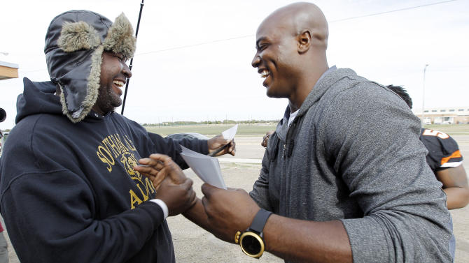 Dallas defensive lineman DeMarcus Ware, right, greets a Lancaster resident as he leads the captains of the Lancaster Tigers high school football team, not pictured, around town to drum up support among the residents for their upcoming playoff game during the Duracell Trust Your Power NFL Campaign event on Tuesday, Nov. 13, 2012inLancaster, Texas. (Photo by Brandon Wade/Invision for Duracell/AP Images)
