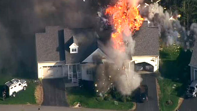 In this frame grab from television helicopter video, a police SWAT team, left, is parked on the lawn of a home in Brentwood, N.H., as it explodes in flames, Monday May 12, 2014. Shots were fired just before the fire, which involved a police officer, according to the New Hampshire State Police. (AP Photo/WCVB-TV 5) TV OUT