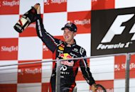 SINGAPORE - SEPTEMBER 23: Sebastian Vettel of Germany and Red Bull Racing celebrates on the podium after winning the Singapore Formula One Grand Prix at the Marina Bay Street Circuit on September 23, 2012 in Singapore, Singapore. (Photo by Paul Gilham/Getty Images)