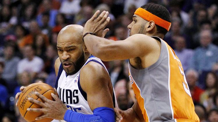 Dallas Mavericks' Vince Carter, left, drives past Phoenix Suns' Jared Dudley during the first half of an NBA basketball game, Thursday, March 8, 2012, in Phoenix. (AP Photo/Matt York)
