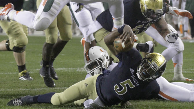 Notre Dame quarterback Everett Golson (5) scrambles to the one yard line and is tackled by Miami linebacker Eddie Johnson during the first half of an NCAA college football game at Soldier Field Saturday, Oct. 6, 2012, in Chicago.(AP Photo/Charles Rex Arbogast)