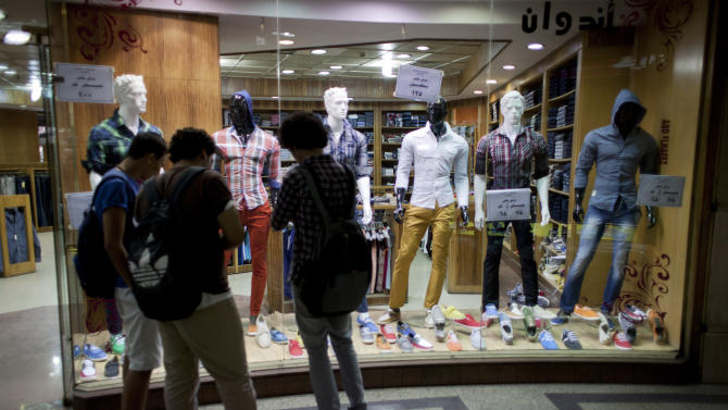 Egyptian men shop inside a commercial mall in Cairo, Egypt, Wednesday, Oct. 31, 2012. Egypt's capital prides itself on being city that never sleeps, with crowds filling cafes and shops open into the small hours. So the government is facing a backlash from businesses and the public as it vows to impose new nationwide rules closing stores and restaurants early. Officials say the crisis-ridden nation has to conserve electricity, but they also seem intent on taming a population they see as too unruly.  (AP Photo/Nasser Nasser)