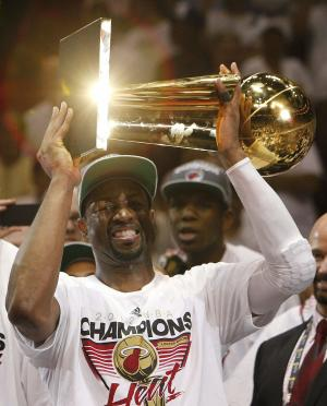 Miami Heat shooting guard Dwyane Wade holds the the Larry O'Brien NBA Championship Trophy after Game 5 of the NBA finals basketball series against the Oklahoma City Thunder, Friday, June 22, 2012, in Miami. The Heat won 121-106 to become the 2012 NBA Champions.(AP Photo/Lynne Sladky)