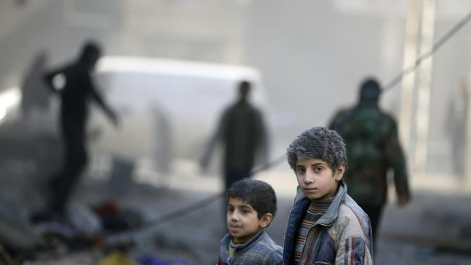 Children covered with dust walk at a site hit by what activists said was an air strike by forces of Syria's President al-Assad in the Duma neighbourhood of Damascus