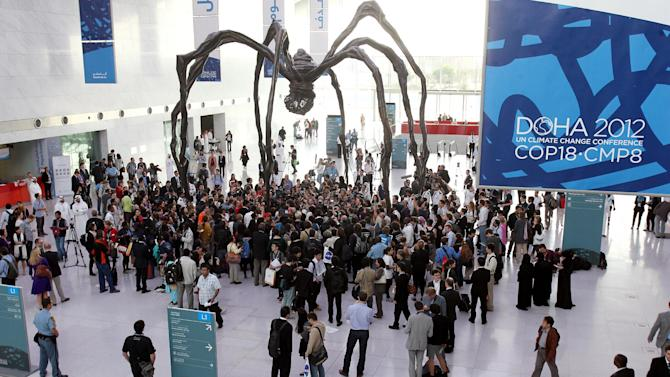 Local and international activists march inside a conference center under a giant statue of a spider to demand urgent action to address climate change at the U.N. climate talks in Doha, Qatar, Friday, Dec. 7, 2012. A dispute over money clouded U.N. climate talks Friday, as rich and poor countries sparred over funds meant to help the developing world cover the rising costs of mitigating global warming and adapting to it. (AP Photo/Osama Faisal)