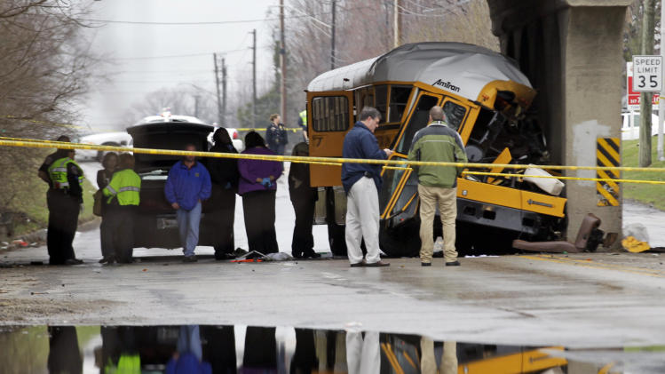 Investigators look over the scene of a fatal bus crash on the southeast side of Indianapolis, Monday, March 12, 2012. The driver and one student were killed and two others critically injured.  (AP Photo/Michael Conroy)