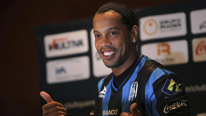Brazil's Ronaldinho poses for a photo after slipping on his new Queretaro soccer club jersey at a press conference in Mexico City, Friday, Sept. 12, 2014. Mexican first-division club Queretaro signed the former 34-year-old soccer star, who had been without a club since leaving Brazil's Atletico Mineiro in July and had been negotiating with several clubs. The two-time FIFA world player of the year helped Atletico Mineiro win last year's Copa Libertadores for the first time. (AP Photo/Marco Ugarte)